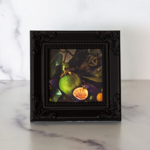 Photograph of a black frame with a photograph of passion fruit and figs