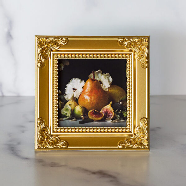 Photograph of a gold frame with a photograph of pears and figs