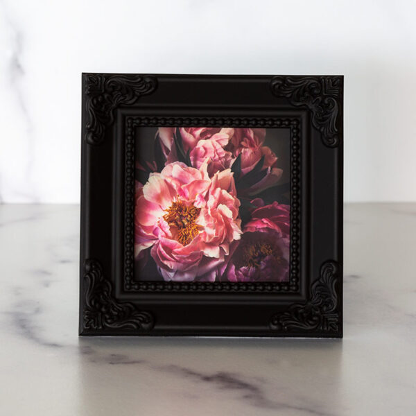 Photograph of a black frame with a photograph of peonies