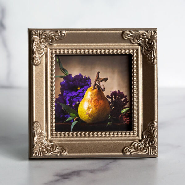 Photograph of a champagne colored frame with a photograph of a pear and purple flowers