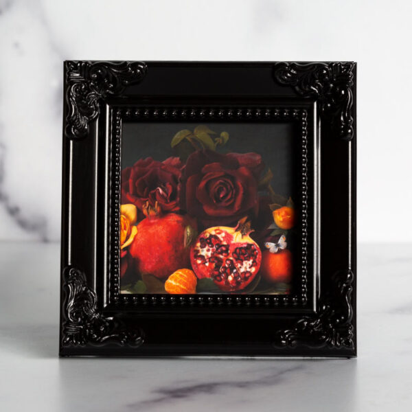 Photograph of a black frame with a photograph of pomegranate and roses