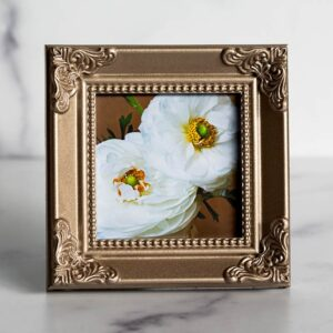 Photograph of a champagne colored frame with a photograph of white ranunculus