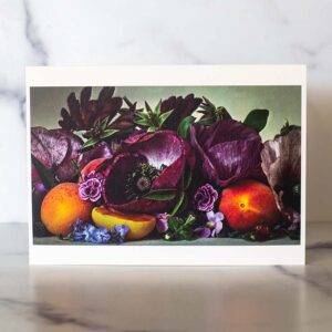 Photograph of a greeting card with purple poppies and apricots on it.