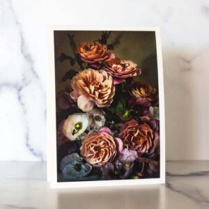 Photograph of a greeting card with pink roses and multi colored poppies on it.